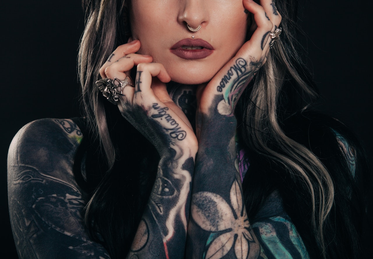 A woman with a nose piercing and tattoos on her arms, hands and neck